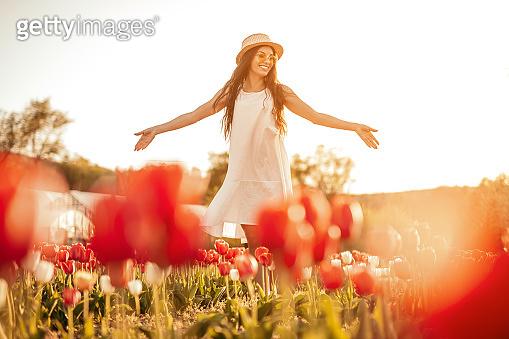 Relaxed positive woman spreading hands walking on flower field