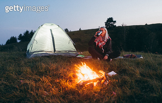 Young woman camping and resting at night by campfire