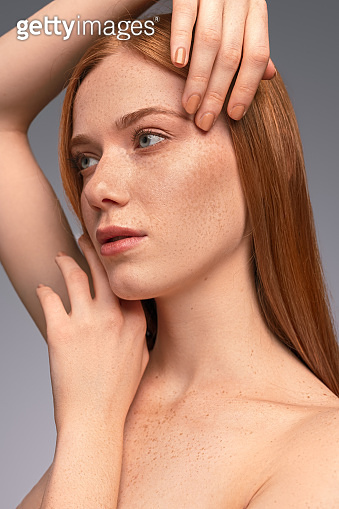 Freckled woman touching clean face