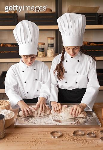 Enthusiastic children in cook uniform kneading dough