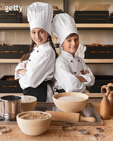 Confident little bakers working in kitchen