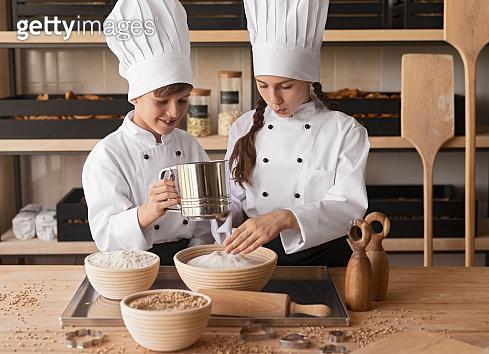 Little bakers sieving flour together