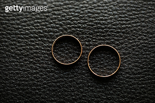 Macro image of two wedding rings isolated on black leather background.