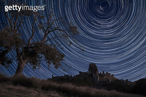 Digital composite image of star trails around Polaris with Beautiful old castle ruin landscape