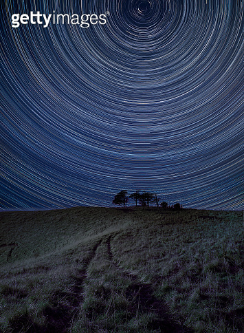 Digital composite image of star trails around Polaris with Vibrant landscape of hill and trees in countryside