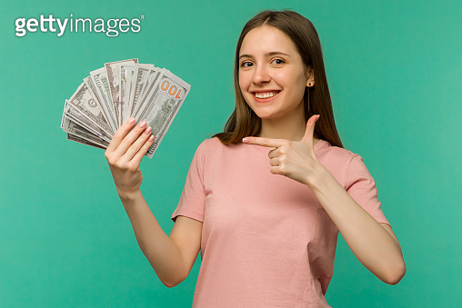 Portrait of a cheerful young woman holding money banknotes and celebrating
