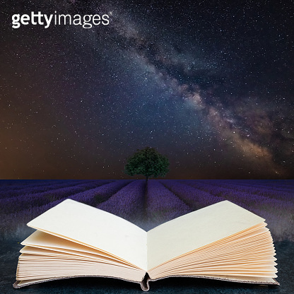 Digital composite concept image of open book wth Vibrant Milky Way composite image over landscape of Beautiful lavender field