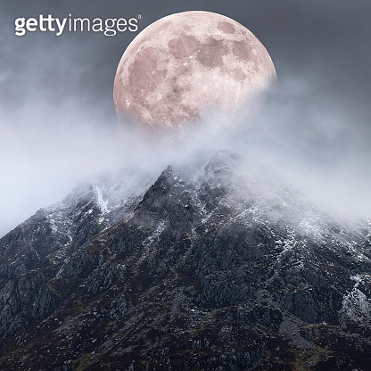 Epic digital composite image of Supermoon above mountain range giving very surreal fantasy look to the dramatic landscape image