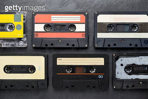 Black audio tape compact cassettes on black background