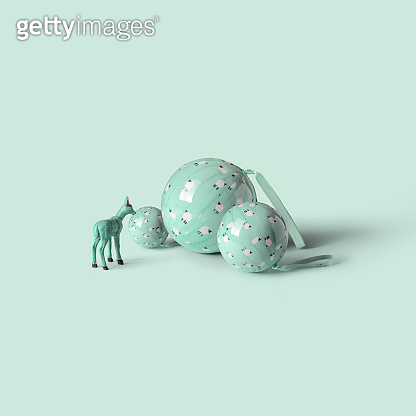 Reindeer standing on Christmas balls, on green mint background. Minimal concept