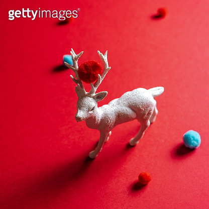 White reindeer toy with small balls of wool on red background.