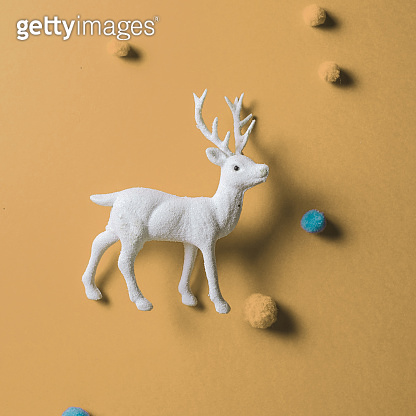 White reindeer toy with small balls of wool on pastel yellow background.