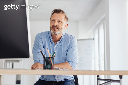Businessman sitting working at a large monitor