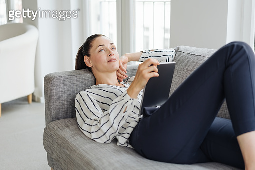 Young woman lying on a sofa daydreaming