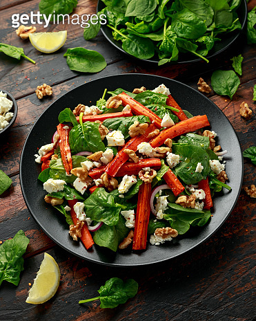 Roasted carrot salad with feta cheese, walnut and spinach. healthy food