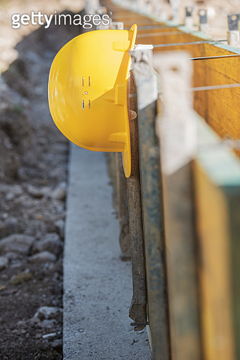 Yellow hardhat helmet hanging from supported wooden panels on a building site