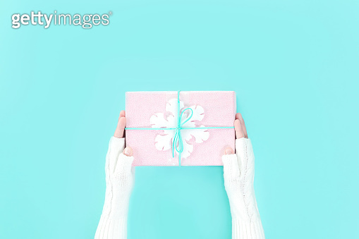 Hands in mittens holding winter gift box with snowflake