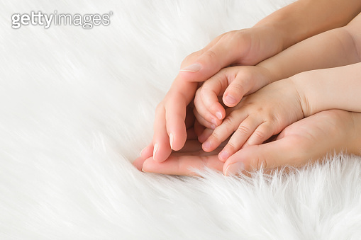 Baby hands in young mother palms on white, soft, fluffy fur blanket background. Lovely, emotional, sentimental moment. Closeup.