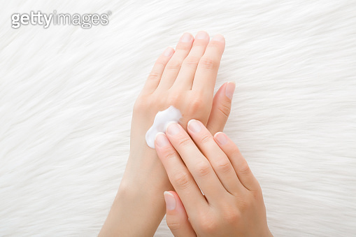 Young perfect adult woman hands using moisturizing cream on light white fluffy fur blanket background. Care about clean and soft body skin. Daily beauty product. Closeup. Point of view shot. Top view.