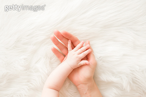 Infant hand on mother palm on white fluffy fur background. Lovely, emotional, sentimental moment. Trust and care concept. Closeup. Top down view.