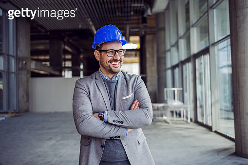 Portrait of handsome successful architect standing with arms crossed in building in construction process.