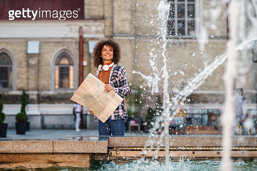 Young attractive mixed race woman behind fountain, looking at it and holding map.