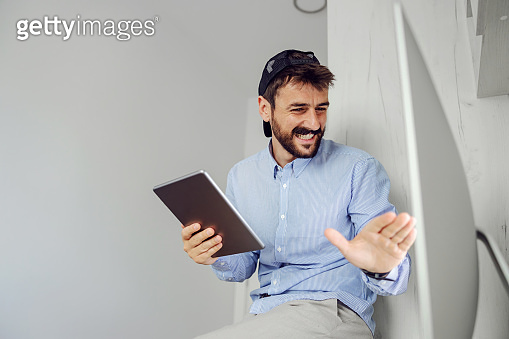 Young bearded smiling man dressed business casual sitting and using tablet in office.