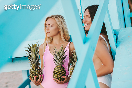 Girls friends having fun with pineapples on beach party