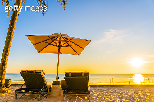 Beautiful tropical nature umbrella chair with palm tree around beach sea ocean at sunset or sunrise