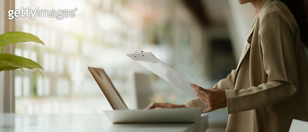 Side view of female office worker working with laptop and paperwork on table