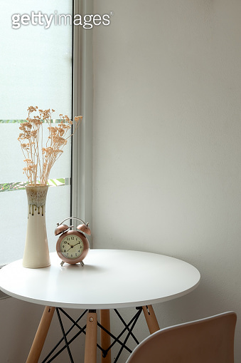 Cropped shot of modern home interior design with flower vase, clock and copy space