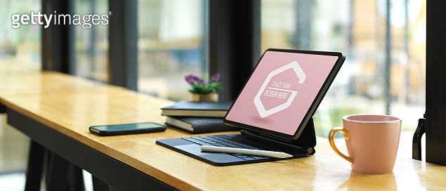 Portable workspace with mock up digital tablet, supplies and coffee mug