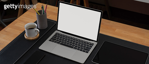 Modern workspace with mock-up laptop, stationery and coffee cup on wade table