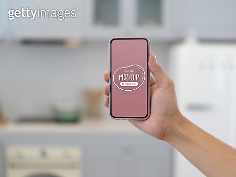 Male hand holding mock up smartphone in blurred kitchen room background