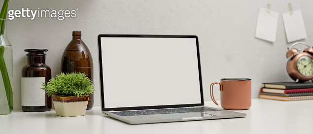 Mock up laptop on modern workspace with cup, books and decorations