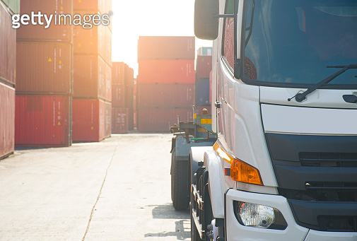Head of haulage truck with container depot at the background as for industry, transportation and logistics concept.