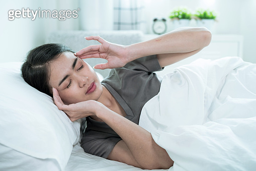 An Asian woman wakes up early with a headache, dizziness, Migraine, Tension.