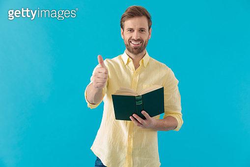 Casual man giving a thumbs up and holding a book