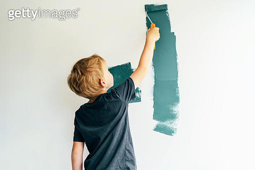 boy paints a wall with a roller