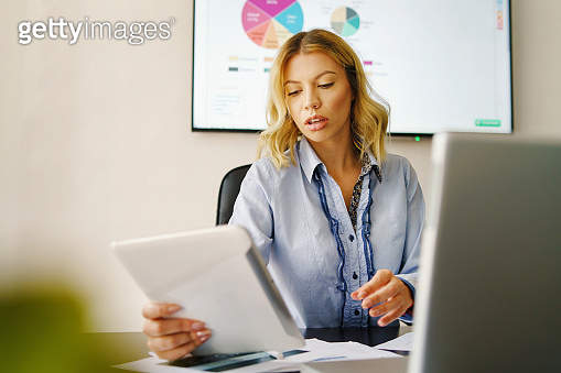 Front view young adult caucasian woman holding digital tablet at work - Businesswoman working at the office in day sitting by the desk - Beautiful female adult using technology checking reports