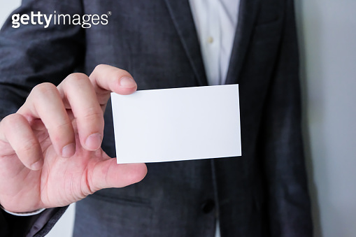 Men business person wearing grey formal suit and white shirt holding Blank white business card mock up template to put name and text on. Advertisement for business concept, contact detail.