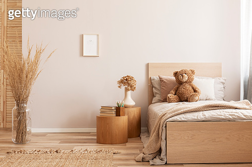 Bright and natural hotel room interior with single bed and wooden nightstand with flowers