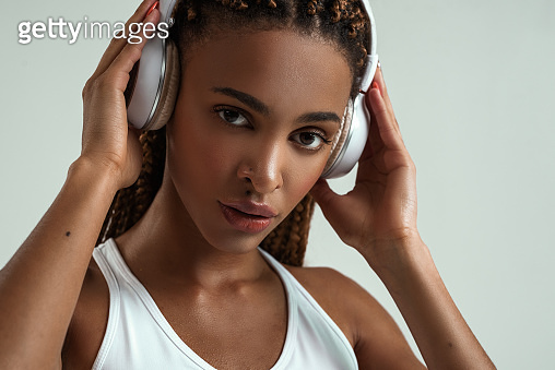 Enjoying music. Cute african woman adjusting headphones and looking at camera while standing against grey background