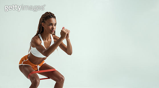 Fitness trainer. Full length of young and slim african woman in sports clothing exercising with a resistance band in studio against grey background