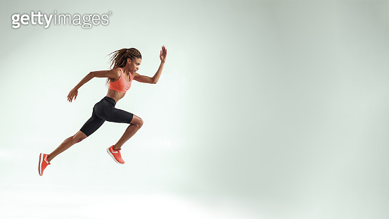 Never give up. Full length of young african woman with perfect body in sports clothing jumping in studio against grey background