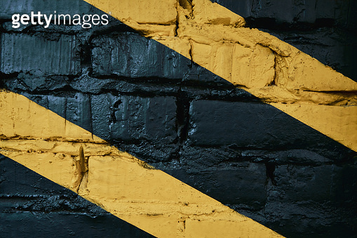 Black brick wall with yellow stripes at gym