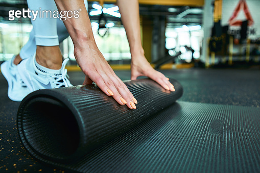 Cropped shot of a fitness woman in sportswear rolling yoga mat while working out at gym