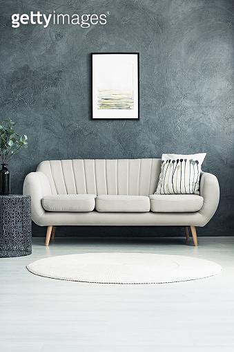 Beige sofa against concrete wall