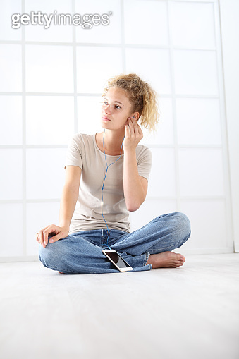 young woman with mobile phone sitting on the floor dressed casual with curly and long red hair isolated on white window background