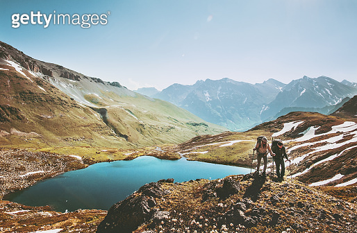 Couple backpackers hiking in mountains over lake Traveling together Lifestyle wanderlust concept adventure vacations outdoor aerial view